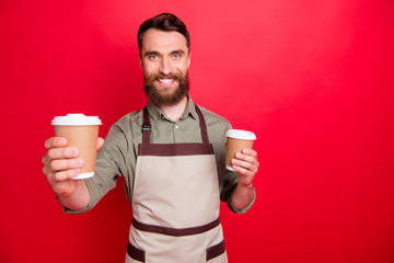 Close-up portrait of his he nice attractive cheerful cheery friendly bearded guy holding in hands inviting offering espresso latte service isolated over bright vivid shine red background