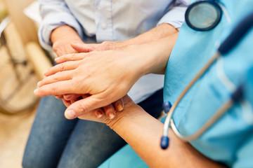 Pflegekraft hält die Hand einer Seniorin
