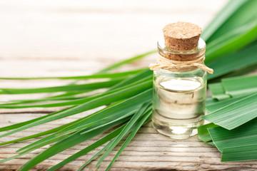 lemongrass essential oil in the bottle, with fresh lemongrass leaves, on the wooden table