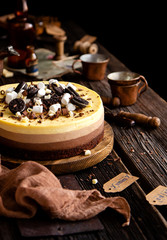 Beautiful still life with homemade delicious three chocolates cheese cake on wooden stand on rustic table