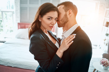 The woman and man in suits hug in the room