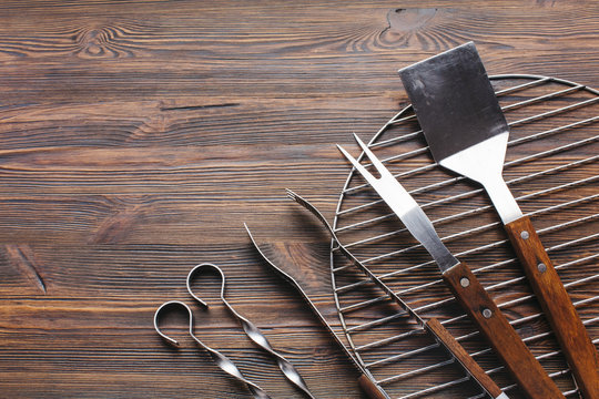 New metallic barbecue utensils on wooden background