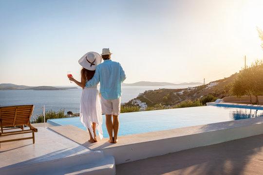 Romantisches Paar steht am Pool und genießt den Sonnenuntergang bei einem Glas Aperitif während des Sommerurlaubes