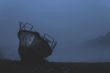 old boat washed ashore in fog