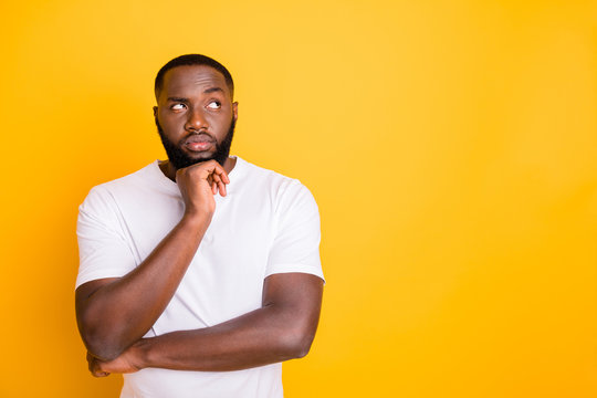 Close up photo of dark skin guy looking up empty space not sure with decision wear casual outfit isolated yellow background