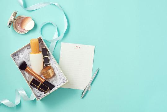 Make up gift box with serum, blush, brushes, cream and lipsticks indoors