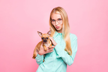 Portrait of lovely woman with eyewear eyeglasses stroking her doggy wearing teal shirt isolated over pink background