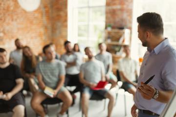 Male speaker giving presentation at university workshop. Audience or conference hall. Using tablet...