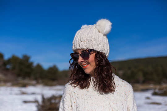 portrait of a young beautiful woman in the snow. Sunny weather. Wearing warm clothes. Winter lifestyle
