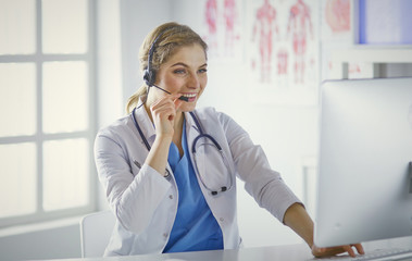 Portrait of a happy smiling young doctor in headset in office