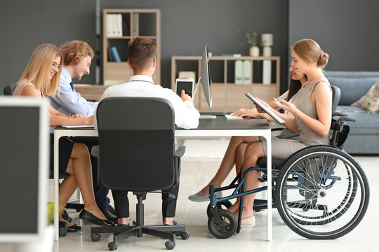 Handicapped young woman with colleagues working in office