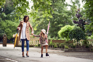 Back to school. Happy mother and daugther go to elementary school. Parent taking child to primary...