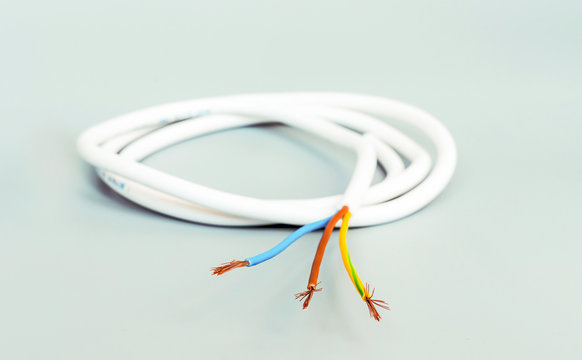 Three-core cable in white isolation on a gray background