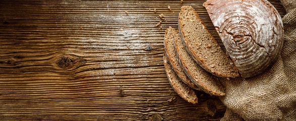 Bread,  traditional spelled sourdough bread cut into slices on a rustic wooden background, close-up, top view, copy space. Concept of traditional leavened bread baking methods Fototapete