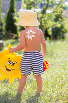 Toddler child with suntan lotion shaped as sun on his back, going at the beach with toys and flufy sun toy