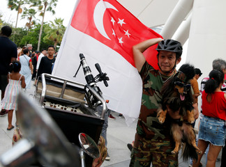 A man poses for a picture with his pet dog during Singapore's 54th National Day Parade in Singapore