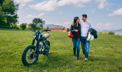 Unrecognizable couple walking on the field embraced and parked motorbike