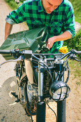 Young man refilling the gas tank of a motorbike outdoors