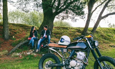 Young couple resting from a motorcycle trip having a beer outdoors with motorbike in foreground. Selective focus on couple in the background
