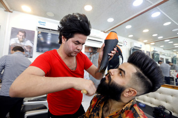 A barber combs a customer's beard at his shop in preparation for Eid Al-Adha celebration in Baghdad