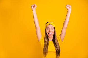 Portrait of content teen raising her fists screaming shouting isolated over yellow background