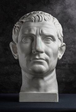 Gypsum copy of ancient statue Augustus head on dark textured background. Plaster sculpture man face.