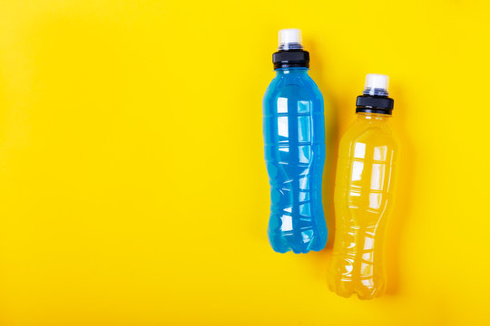 Isotonic energy drink. Bottles with blue and yellow transparent liquid, sport beverage on a colorful background