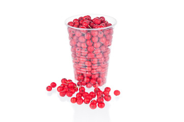 Ripe rowan berries in plastic cup on white background