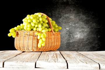 Wooden table background with green bunches of grapes Fototapete
