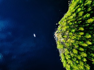 Papiers peints Navire Aerial view of blue lake with a fishing boat and green forests with rocks in Finland.