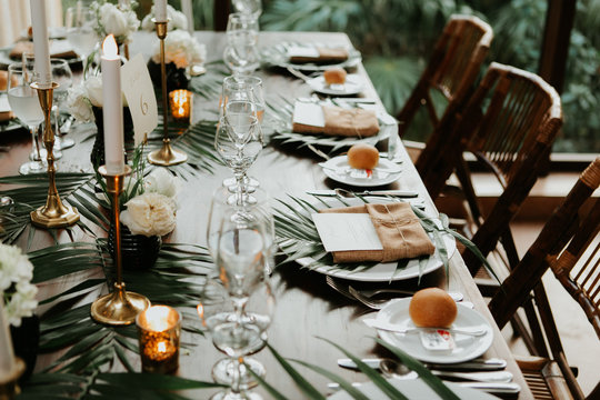 modern and bohemian table decorations at wedding reception, table setting with candle sticks, palm leafs, and flowers