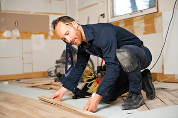Obraz A Male Worker install wood floor on a house - fototapety do salonu