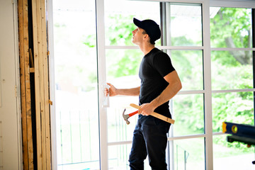 A handsome young man installing Double Sliding Patio Door in a new house construction site Wall mural