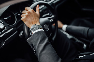 Close up top view of  man's watch in black suit keeping hand on the steering wheel while driving a luxury car.