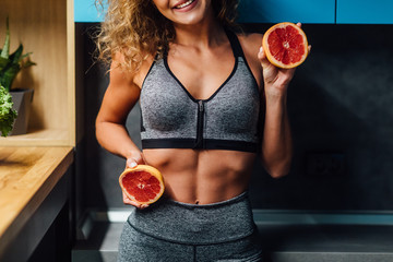 Close up photo. Woman fit girl holding two halfs of grapefruit citrus fruit in hands, covering her boby. Healthy diet food. Happiness holidays fun concept.