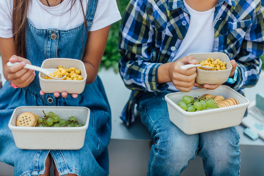 Close up photo. Children with healthy and harmful snacks outside. Child eating maize. Concept of healthy nutrition. Lifestyle.