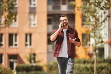 Wall Mural - What a great day Happy bearded man in casual wear and eyeglasses talking by phone and smiling while walking through the city street