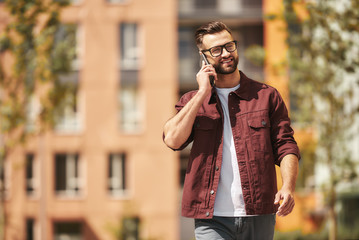 Wall Mural - Good talk. Happy bearded man in casual wear and eyeglasses talking by phone and smiling while walking through the city street