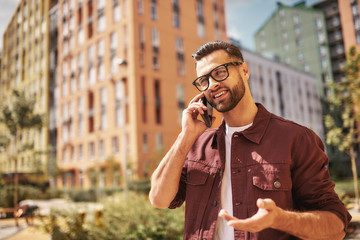 Wall Mural - Great news Happy bearded man in casual wear and eyeglasses talking by phone and smiling while standing on the street