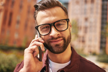 Wall Mural - Nice talk with friend. Close up portrait of happy bearded man in casual wear and eyeglasses talking by phone and smiling while standing on the street