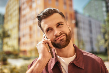 Wall Mural - I don't know. Portrait of thoughtful bearded man talking by phone while standing on the street