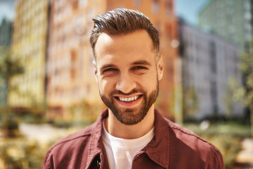 Wall Mural - Hello Portrait of happy attractive man with stubble smiling and looking at camera while standing on the street