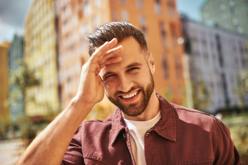 Wall Mural - Sunny day Portrait of happy attractive man with stubble smiling and looking at camera while standing on the street