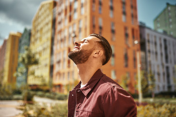 Wall Mural - Feeling so happy Side view of positive attractive man with stubble smiling and looking at the sky while standing on the street