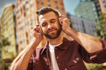 Enjoying my favorite song. Handsome young bearded man in headphones listening to the music and keeping eyes closed while standing on the street Wall mural