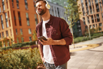 Wall Mural - I love that song. Cheerful young man with stubble in headphones listening to the music and holding mobile phone while standing on the street.