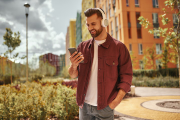 Wall Mural - Playlist settings. Happy young man with stubble in headphones listening to the music and holding mobile phone while standing on the street