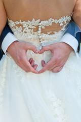 Bräutigam formt ein Herz mit seinen Händen