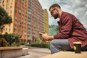 Wall Mural - Chatting with friend. Handsome man with stubble in casual clothes holding mobile phone and drinking coffee while sitting on the bench outdoors