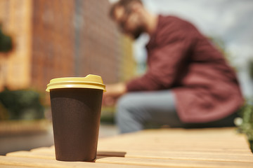 Wall Mural - Fresh coffee. Blurred photo of a man with stubble in casual clothes holding mobile phone. Cup of coffee on the bench